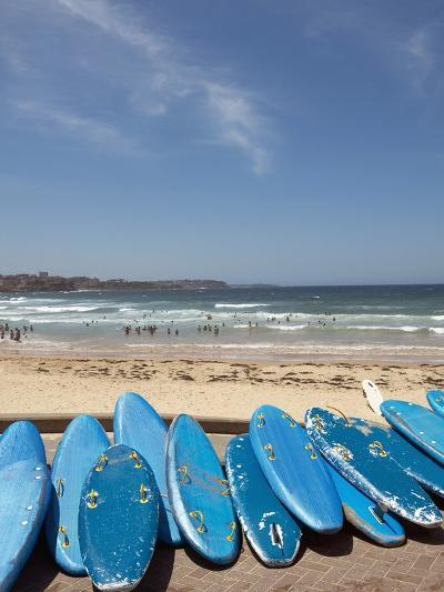 View of stacked up surfboards at the beach--Photographic Print
