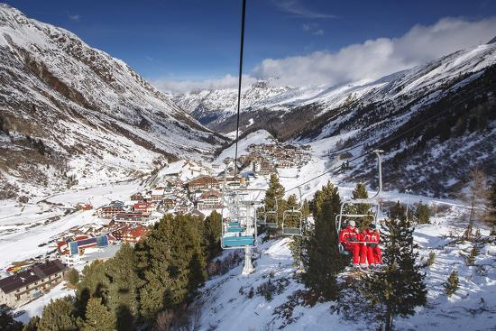 Village of Obergurgl Sat at Top of Otztal Valley as Skiers Ascend Mountain on Chairlifts-Garry Ridsdale-Photographic Print