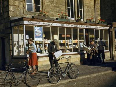 Villagers Read Newspapers Near Bicycles Outside a Book Shop-Melville Grosvenor-Photographic Print
