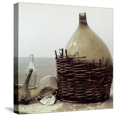 Demijohn and Glass Flasks Left on the Seashore