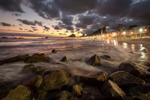Beautiful Landscape in Leme Beach Seen from the Sand with Water Rolling over Rocks and Sunset Cloud by Vitor Marigo