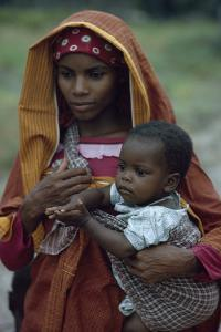 A young woman of Arab descent holds her young child. by Volkmar K. Wentzel