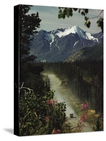 A Camper Rolls Down a Dirt Road Below High Mountains in Alaska