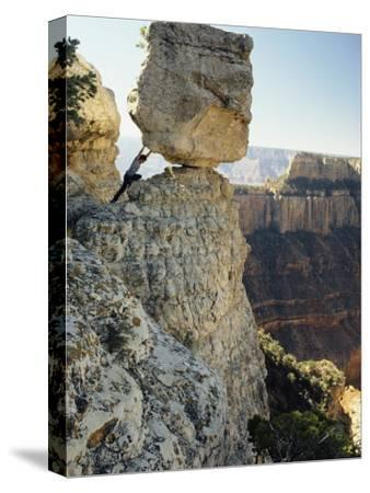 A Man Pretends to Push a Huge Boulder into the Canyon