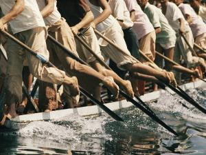 Men Paddle a Boat During a Race on Inle Lake by W.E. Garrett