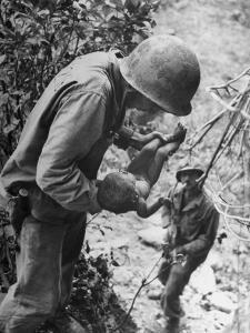 American Lieutenant Carrying Micronesian Baby He Found in cave Japanese Soldiers Holed Up There by W. Eugene Smith