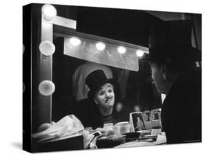 Charlie Chaplin Looking Into Mirror, Putting on Makeup for Role as the Animal Trainer by W. Eugene Smith