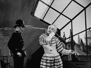 Charlie Chaplin Squirting Water Into Face of Policeman, Scene from Limelight by W. Eugene Smith
