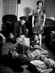 Country Dr. Ernest Ceriani Tucking Blanket around 82-Year-Old Man Dying of a Heart Attack in Parlor by W. Eugene Smith