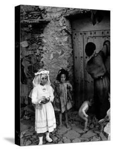 Lorenza Curiel in White First Communion Dress Waiting for Mother to Lock Door by W. Eugene Smith