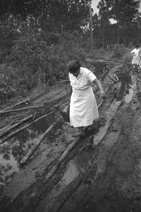 Nurse Maude Callen Carrying Her Medical Bag Along a Muddy Road after Caring for a Patient, 1951 by W. Eugene Smith