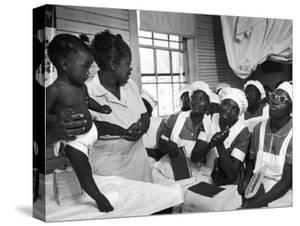 Nurse/Midwife Maude Callen Holds Baby and Teaches Class in Midwifery How to Look for Abnormalities by W. Eugene Smith