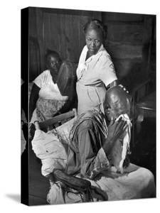 Nurse Midwife Maude Callen Tenderly Caring for an Old Chair-Bound Paralytic Touched by Her Kindness by W. Eugene Smith
