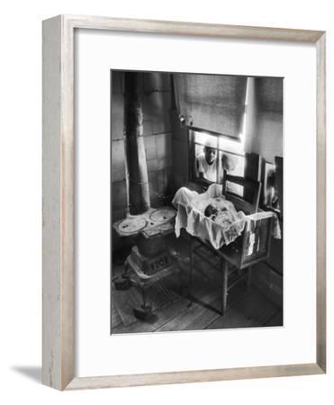 Victoria Cooper's Children Peering in Window Where Newborn Baby Lies in Crib Made from Fruit Crate