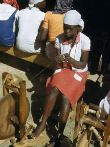 Girl at a Training School Spins Thread at a Wooden Spinning Wheel by W. Robert Moore