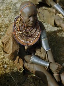 Seated Masai Woman Wears Large Arm Bands, Necklaces, and Earrings by W. Robert Moore