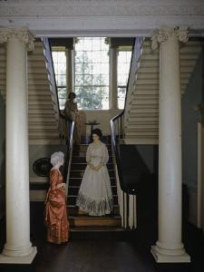 Three Women Wearing Colonial Dresses Stand in an Old Mansion by W. Robert Moore