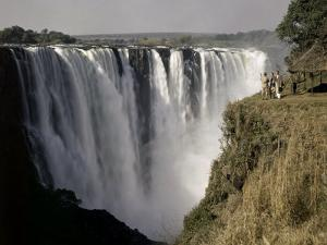Tourists Look Small Against Backdrop of Victoria Falls by W. Robert Moore