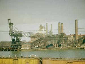 Photo Taken from Window of a Train Showing Industrial Waterfront Scene by Walker Evans