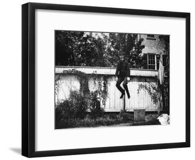 Man in a Suit and Bowler Hat Jumping in the Air in a Backyard in Brooklyn, Ny