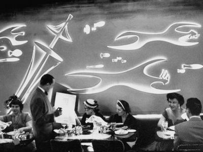 Dimly Lit Wall of the Sea Restaurant, with Customers Reading Their Menus with Flashlights by Wallace Kirkland