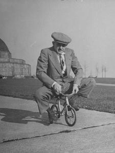 Humorous of Man Riding Tiny Bicycle by Wallace Kirkland