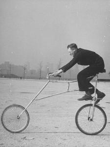 Inventor Maurice Steinlauf Riding Eccentric Bike with Roving Front Wheel by Wallace Kirkland