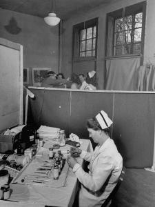 Nurse Sitting at Table with Medical Supplies While Doctors Examine Patient in Background by Wallace Kirkland