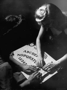People Playing with a Ouija Board by Wallace Kirkland