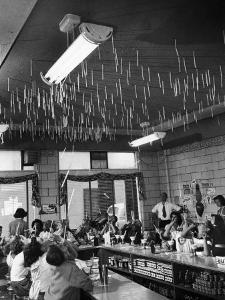 Soda Fountain Proprietor Watching as Kids Use Drinking Straw Covers as Straw Blowgun Missiles by Wallace Kirkland