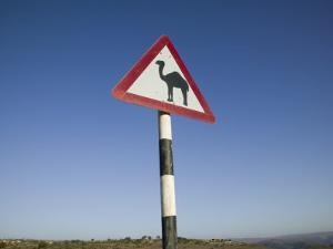 Oman, Dhofar Region, Salalah, Camel Crossing Sign in the Dhofar Mountains by Walter Bibikow