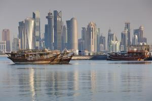 Qatar, Doha, Dhows on Doha Bay with West Bay Skyscrapers, Dawn by Walter Bibikow