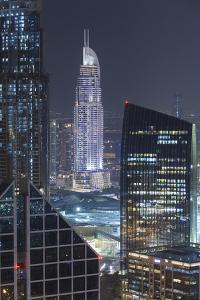 UAE, Downtown Dubai. Downtown cityscape at night lit in blue. by Walter Bibikow