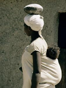 A Xhosa Woman Balances a Container on Her Head and a Baby on Her Back by Walter Meayers Edwards