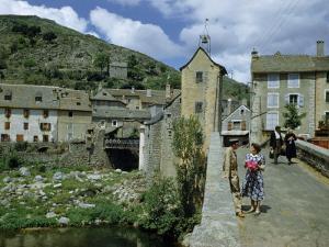 People in Riverside Village Walk across an Old Bridge by Walter Meayers Edwards