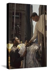 A Pair of Push Boys Unload Racks of Dresses on 7th Avenue, New York, New York, 1960 by Walter Sanders