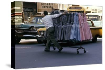 A Push Boy Steers a Rack of Dresses across an Intersection, New York, New York, 1960