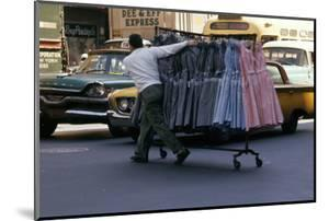 A Push Boy Steers a Rack of Dresses across an Intersection, New York, New York, 1960 by Walter Sanders