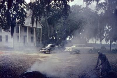 A Woman Rakes and Burns Brush in Front of a Church on Edisto Island, South Carolina, 1956