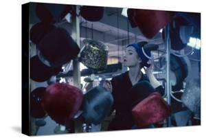 Fashion Model Katherine Gill Tries on a Hat at Christian Dior, New York, New York, 1960 by Walter Sanders
