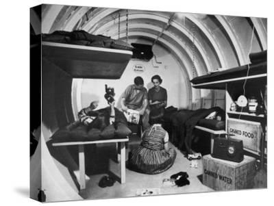 Interior View of Steel Underground Radiation Fallout Shelter Where Couple Relaxes with 3 Children