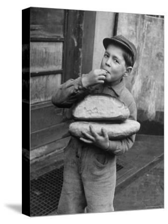 Little Boy Holding Loaves of Bread