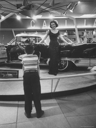 Model Posing Beside Cadillac Eldorado Captures Attention of Young Boy at National Automobile Show