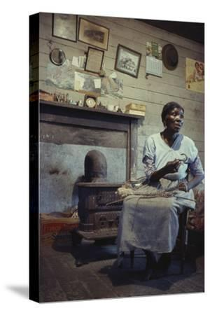 Woman with Cotton Stalks Beside a Wood-Burning Stove, Edisto Island, South Carolina, 1956