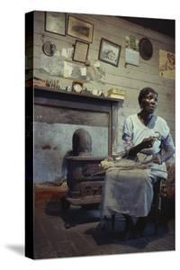 Woman with Cotton Stalks Beside a Wood-Burning Stove, Edisto Island, South Carolina, 1956 by Walter Sanders