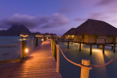 Warmly Lit Over-The-Water Bungalows at a Tropical Resort at Dusky-Sergio Pitamitz-Photographic Print