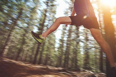 Runner Jumping on Trail Run in Forest for Marathon Fitness