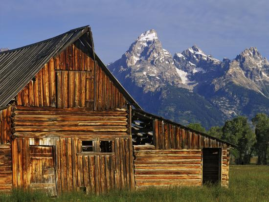 Weathered Wooden Barn Along Mormon Row with the Grand Tetons in Distance, Grand Teton National Park-Dennis Flaherty-Photographic Print