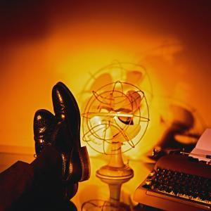 Feet Resting on Desk with Vintage Fan and Typewriter by Wendy Idele