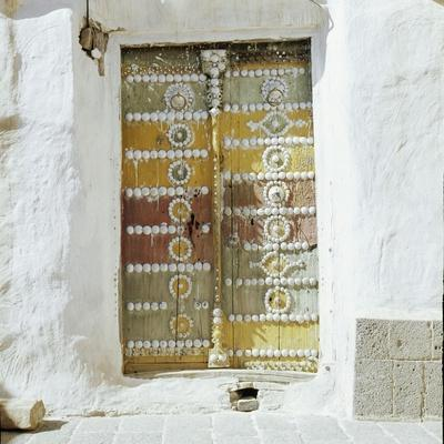Old polychrome door set in whitewashed walls